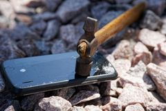 Broken glass of smartphone with hammer on gravel stones. Selective focus.  stock images