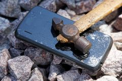 Broken glass of smartphone with hammer on gravel stones. Selective focus.  royalty free stock photos
