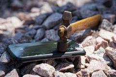 Broken glass of smartphone with hammer on gravel stones. Selective focus.  stock image