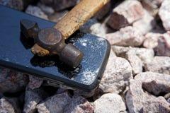 Broken glass of smartphone with hammer on gravel stones. Selective focus.  stock photos