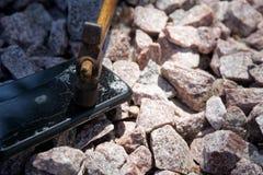 Broken glass of smartphone with hammer on gravel stones. Selective focus.  stock photo