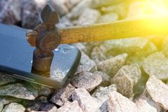 Broken glass of smartphone with hammer on gravel stones. Selective focus and sun beam lights.  royalty free stock photography