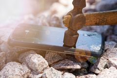 Broken glass of smartphone with hammer on gravel stones. Selective focus and sun beam lights.  stock images