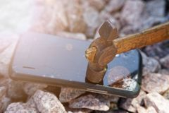Broken glass of smartphone with hammer on gravel stones. Selective focus and sun beam lights.  stock photo