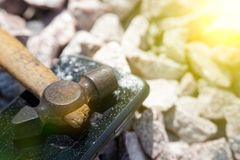 Broken glass of smartphone with hammer on gravel stones. Selective focus and sun beam lights.  royalty free stock photos