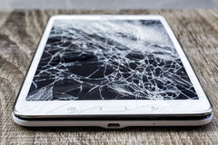 Broken glass of tablet on the grunge wood. Selective focus. Low. Depth of field royalty free stock photography