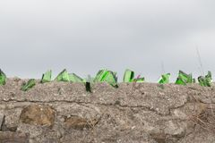 Broken glass on top of an ancient wall royalty free stock photos
