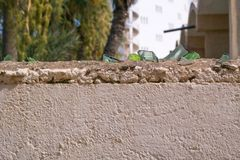Broken glass on the top of the wall. Tunis. Susse security sharp danger piece edge fence protection border barrier blue old boundary forbidden private barbed stock photography