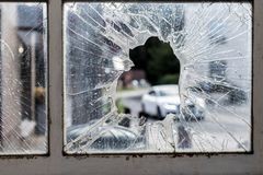 Broken glass window surrounded by rusty old frames with cars and a park on the background