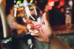 A broken glass with wine female hand close up. stock image