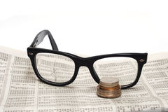 Broken glasses  and coin on stock report Stock Photo