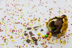 Broken golden chocolate easter eggs with colorful chocolates inside on white background with colorful blurred confetti royalty free stock image