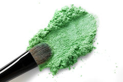 Broken green eye shadow and makeup brush isolated on white background Stock Photography