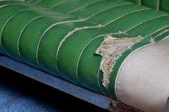 Broken green leather sofa