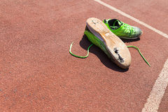 Broken green running shoes. A pair of broken green running shoes with big holes in the sole laying on a running track Stock Photos