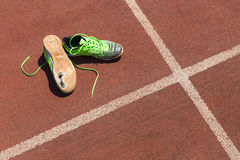 Broken green running shoes. A pair of broken green running shoes with big holes in the sole laying on a running track Royalty Free Stock Image
