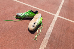 Broken green running shoes. A pair of broken green running shoes with big holes in the sole laying on a running track Royalty Free Stock Images