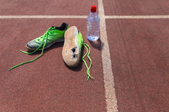 Broken green running shoes with water bottle. A pair of broken green running shoes with big holes in the sole laying on a running track besides a water bottle Royalty Free Stock Image