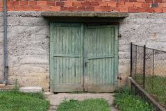 Broken green wooden garage doors with rusted metal hinges and small door handle mounted on concrete wall of red bricks house. With uncut grass and metal fence royalty free stock photos