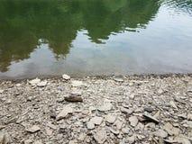 Broken grey rocks and water at shore of river or lake royalty free stock image