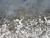 Broken grey rocks and water at shore of river or lake stock image