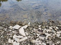 Broken grey rocks and water at shore of river or lake royalty free stock photography