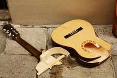 Broken guitar. Pieces of a  on the cement pavement royalty free stock photo