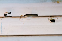 Broken hail siding. Broken in various places hail white siding Royalty Free Stock Images