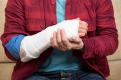 Broken hand. Man in red shirt sitting on couch and holding his broken hand royalty free stock photo