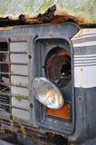 Broken Headlight. A mangled headlight dangling off a rusty, abandoned bus in Honduras Stock Photo