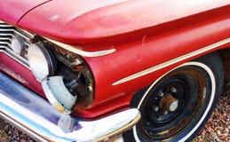Broken headlight on old Pontiac. A headlight hanging out of a 60's era Pontiac Royalty Free Stock Image