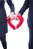 Broken heart. Two handcuffed hands are holding the same broken heart. Image emphasizes a compulsory marriage and a probable divorcing Stock Image