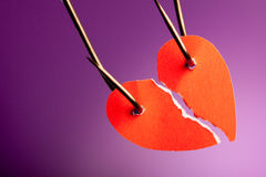 Broken heart. Piece of paper pierced on hook in colored background Royalty Free Stock Photography