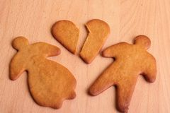 Broken Heart. Gingerbread man and woman with broken gingerbread heart on wooden surface Royalty Free Stock Photo