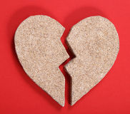 Broken heart. From sand on the red background Stock Photos