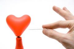 Broken heart. Hand with needle pierces heart balloon Royalty Free Stock Photo