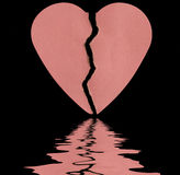 Broken  heart. Broken paper heart on a black background with soft focus reflected in the water Royalty Free Stock Image
