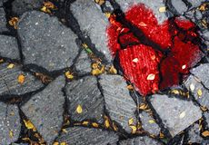 A broken heart on the asphalt. The concept of unhappy love, misunderstanding, sadness, happiness Stock Photos