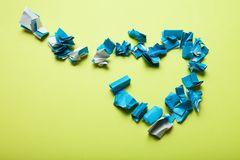 Broken heart from a blue crumpled paper on a yellow background stock illustration