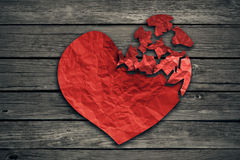 Broken heart breakup concept separation and divorce icon. Red crumpled paper shaped as a torn love on old wood symbol of medical cardiovascular health care Royalty Free Stock Photos
