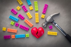 Broken heart breakup concept separation and divorce icon. Red crumpled heart shaped as a torn love on grey floor symbol of medical cardiovascular health care Stock Images
