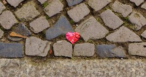 Broken heart on the cobblestone. Broken heart down on the dirty cobblestone footpath in the city Stock Photography