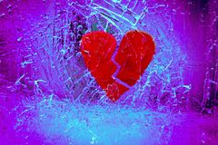 Broken heart in cracked ice. Broken red heart frozen in ice with purple backdrop royalty free stock image