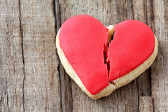 Broken heart. Cracked heart shaped cookie decorated with red icing as a concept of broken heart, breakup and end of relationship Stock Photography