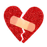 Broken Heart. Glitter ripped heart fixed with adhesive bandage Stock Photo