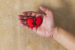 Broken heart in hand. Broken heart in hand with sand background Royalty Free Stock Photography