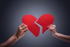 Broken heart. Hands holding broken heart in studio stock photography