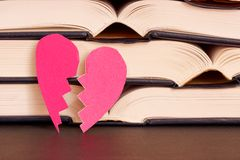 Broken heart literature. Broken pink heart leaning on some open books for your divorce law, love, literature or education concepts - focus is on the heart Stock Images