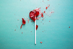 Broken heart lollipop. On a green background stock photos