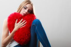 Sad unhappy woman holding red heart pillow Stock Image